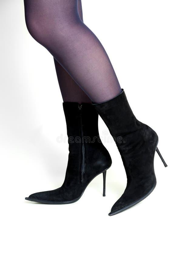 Piernas femeninas delgadas en vista lateral de las botas negras del ante fotografía de archivo libre de regalías