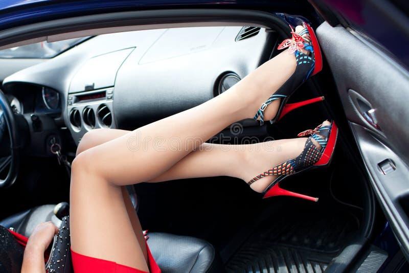 Piernas femeninas en zapatos con los tacones altos en el coche imagen de archivo