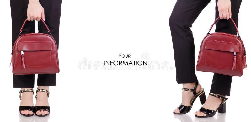 Piernas femeninas en zapatos negros de la laca de los pantalones clásicos del negro con el modelo determinado del bolso de cuero  imagen de archivo libre de regalías