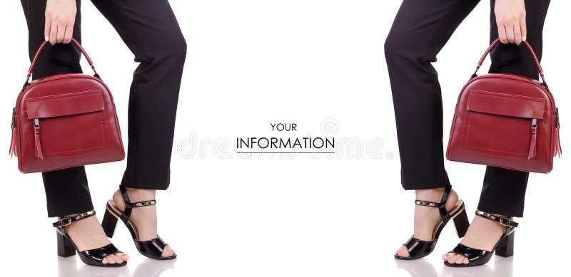 Piernas femeninas en zapatos negros de la laca de los pantalones clásicos del negro con el modelo determinado del bolso de cuero  fotografía de archivo