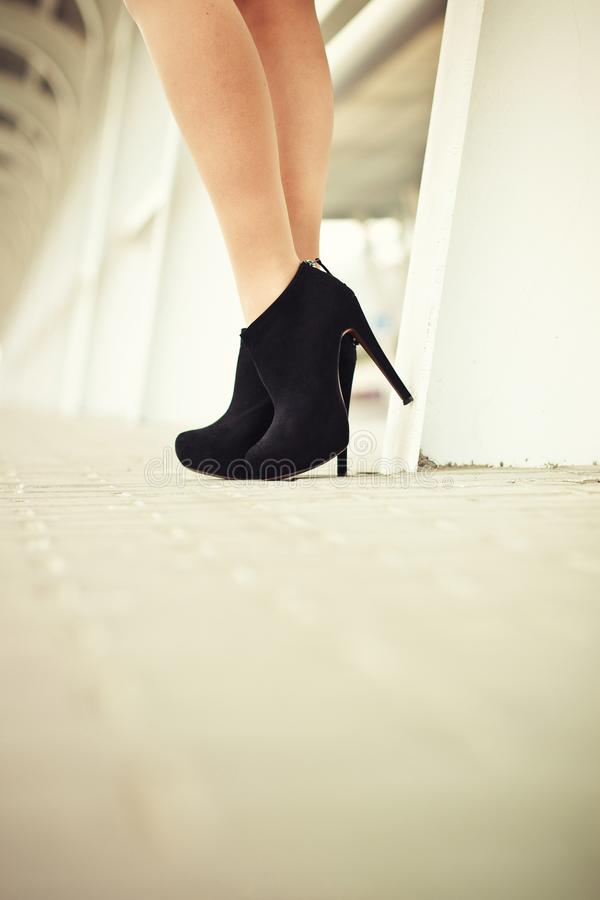 Piernas femeninas en zapatos negros del ante con el pavimento en imagen de archivo libre de regalías