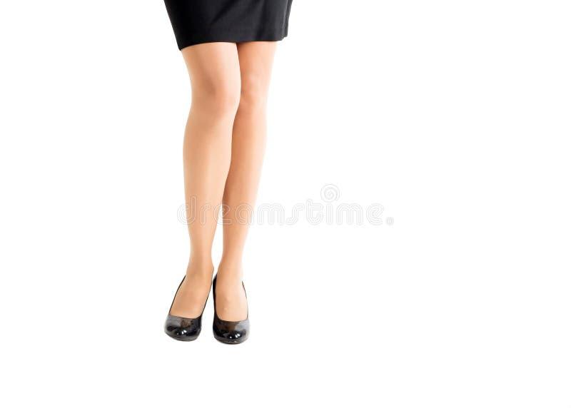 Piernas femeninas hermosas en zapatos clásicos y medias negros del color de piel, aislados en blanco imagen de archivo