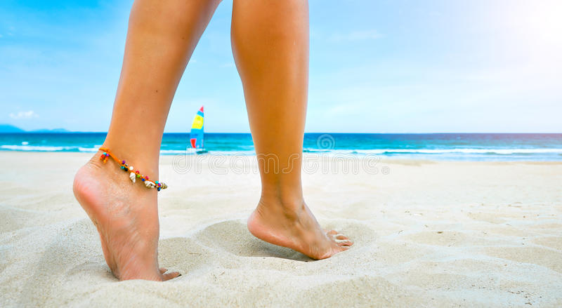 Piernas femeninas jovenes una pulsera en la playa arenosa imagen de archivo libre de regalías