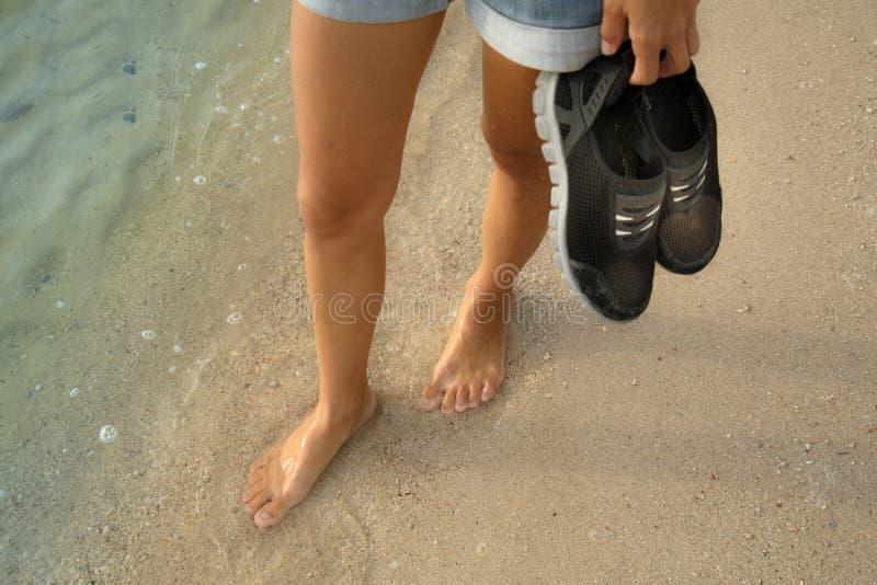 Piernas femeninas que caminan en el agua foto de archivo