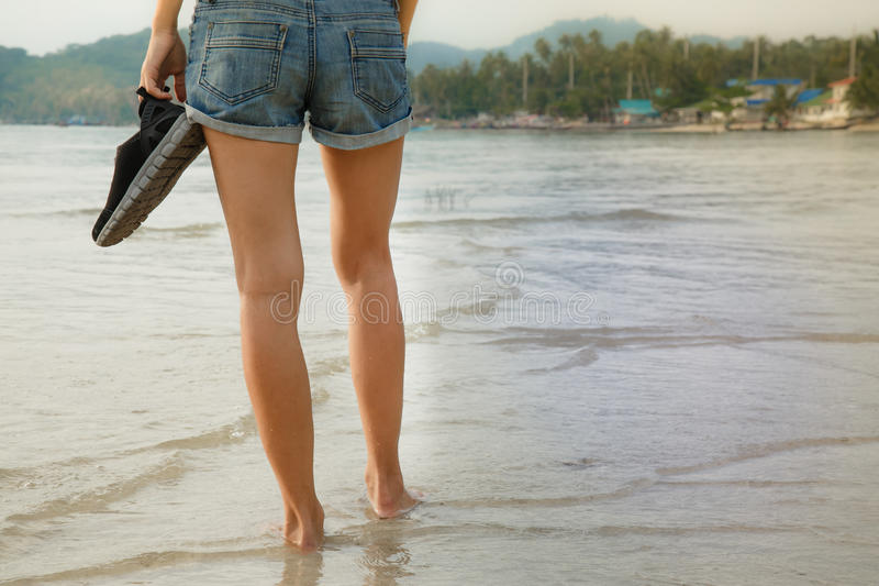 Piernas femeninas que caminan en el agua fotografía de archivo libre de regalías