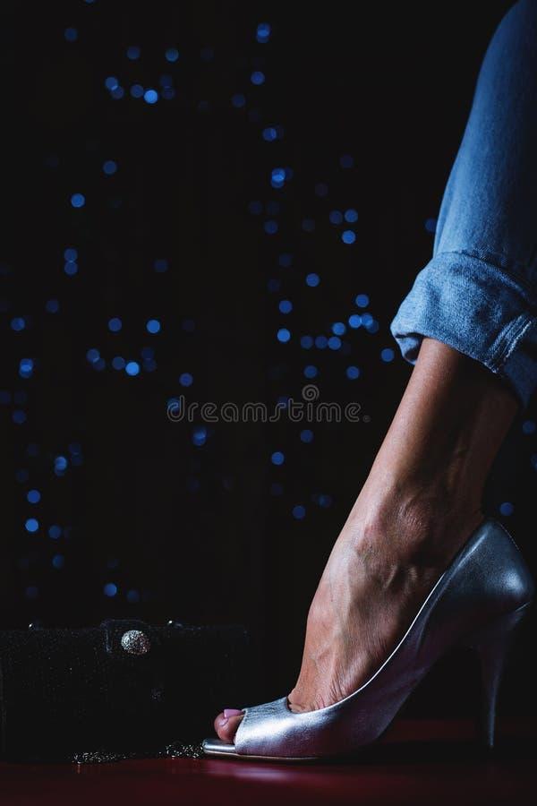 Piernas femeninas que llevan los zapatos y el bolso de plata del tacón alto foto de archivo libre de regalías