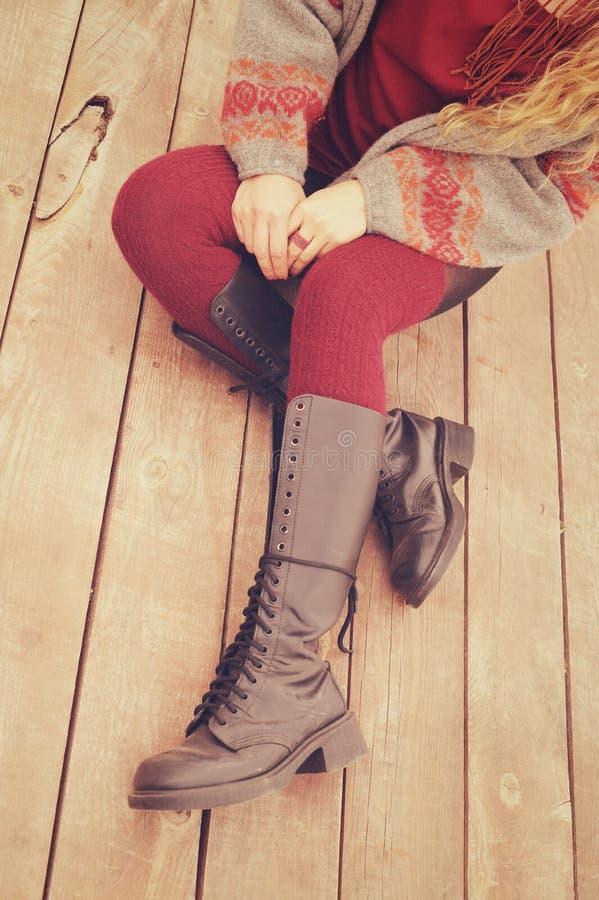 Piernas femeninas vestidas en los zapatos de cuero con los cordones y las medias hechas punto, jersey de la moda y manos con el a foto de archivo libre de regalías