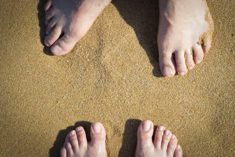 Piernas femeninas y masculinas en la arena, visión superior imagenes de archivo