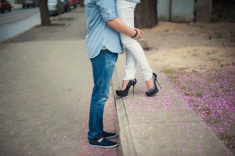 Piernas hermosas de la chica joven en tacones altos al lado del hombre en pétalos rosados de la flor, estilo, moda, concepto, rom foto de archivo libre de regalías