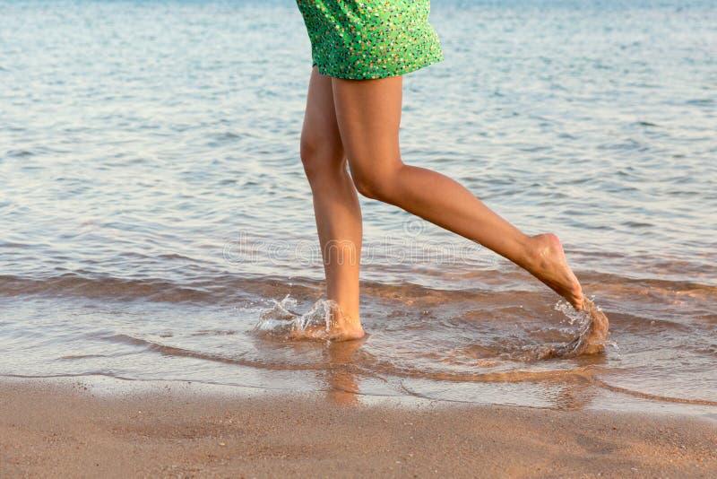 Piernas hermosas de la muchacha que corren en la playa muchacha bonita que camina en el agua fotos de archivo libres de regalías