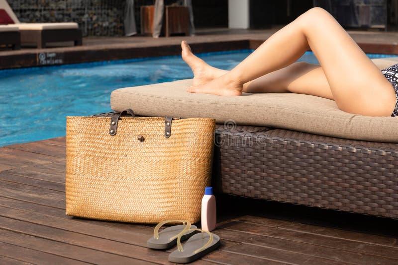 Piernas hermosas de la mujer que mienten en sunbed con el bolso de la playa y protección solar y sandalia imagen de archivo libre de regalías
