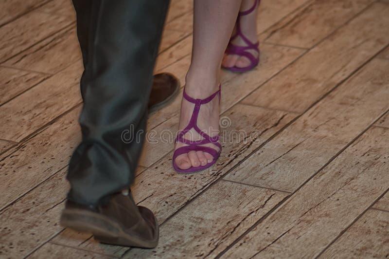 Piernas hermosas de un hombre y de un baile de la mujer en el piso fotos de archivo