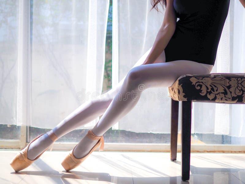 Piernas hermosas del bailarín de ballet que se sientan en la silla y que ponen en sus zapatos del pointe imagen de archivo libre de regalías