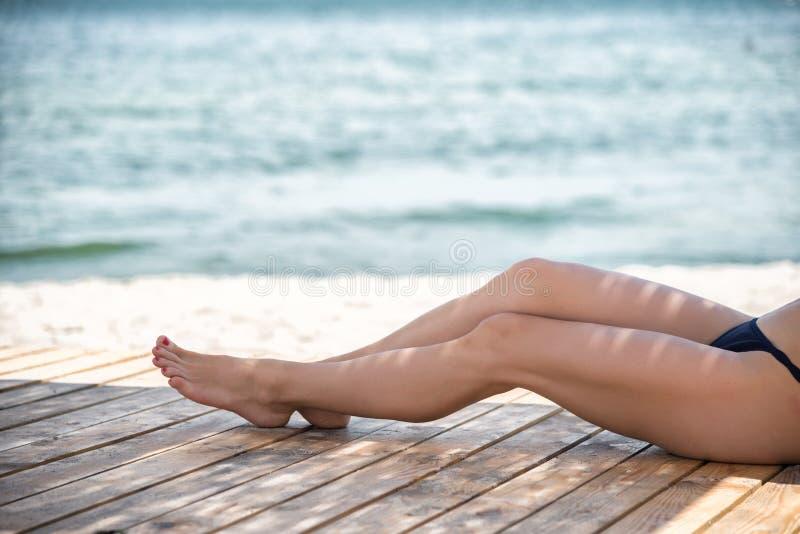 Piernas hermosas del ` s de la mujer en la playa imágenes de archivo libres de regalías