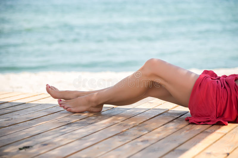 Piernas hermosas del ` s de la mujer en la playa fotografía de archivo libre de regalías