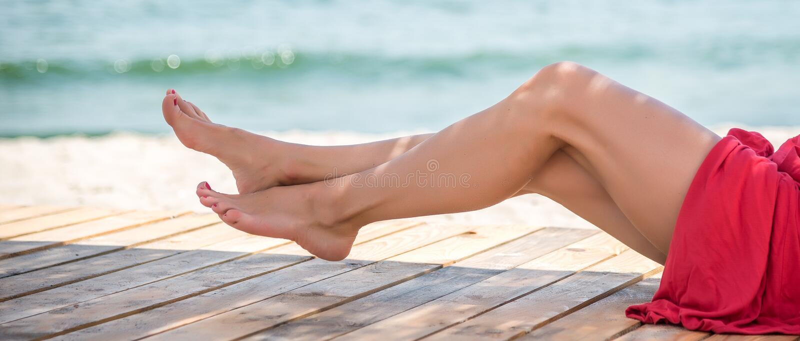 Piernas hermosas del ` s de la mujer en la playa foto de archivo