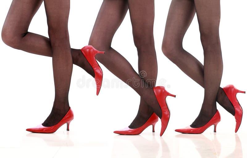 Piernas hermosas en zapatos rojos. imagen de archivo
