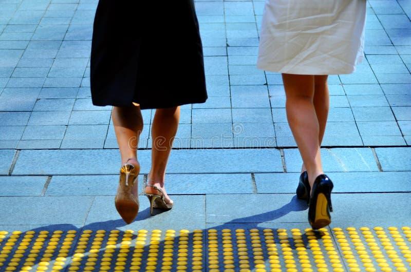 Piernas jovenes de las mujeres de negocios que caminan en la calle de la ciudad junto foto de archivo libre de regalías