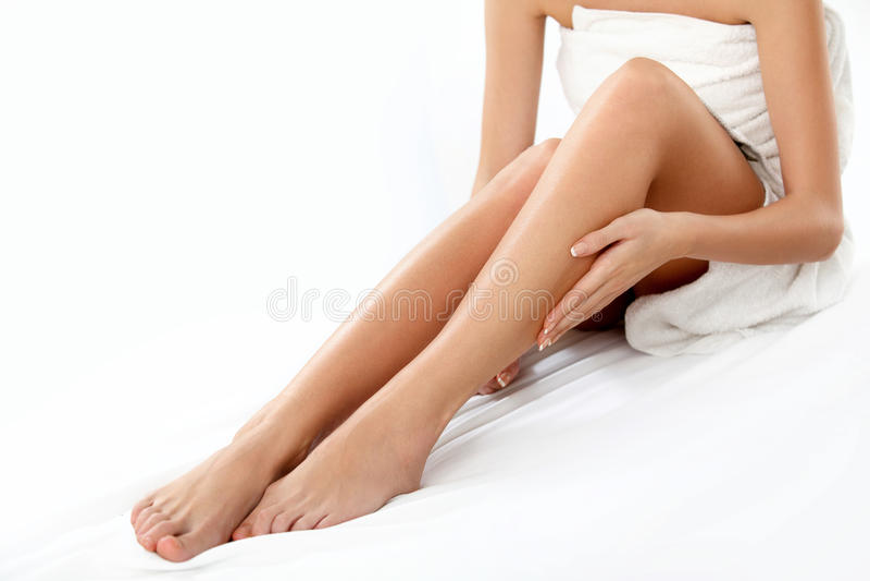 Piernas largas de la mujer aisladas en blanco.  Epilation foto de archivo libre de regalías