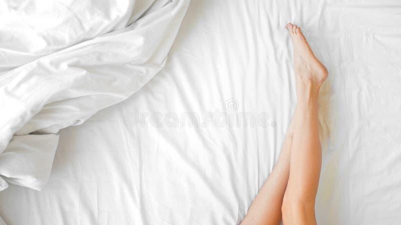Piernas largas de la mujer en la cama Ciérrese para arriba de hembra con la piel sedosa sana perfecta de las piernas después de r imágenes de archivo libres de regalías