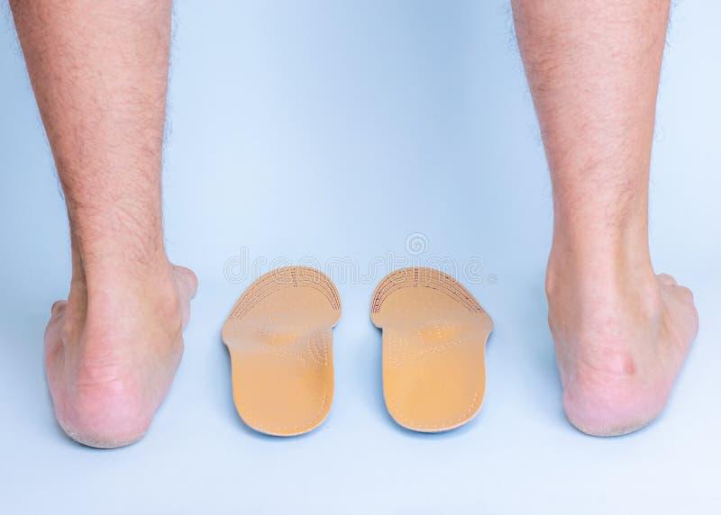 Piernas masculinas con las muestras de pies y de juntas planos y plantillas ortopédicas en un fondo azul imagen de archivo libre de regalías