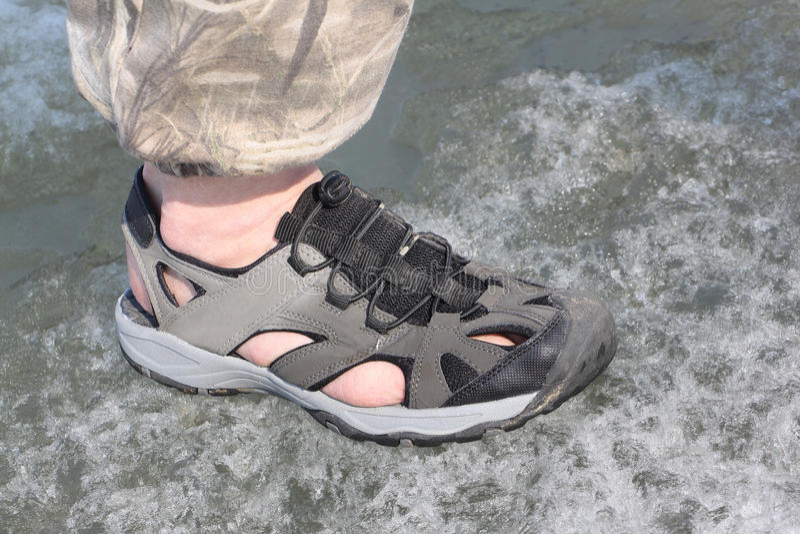 Piernas masculinas en las sandalias para transportar en balsa en el hielo del río imagenes de archivo
