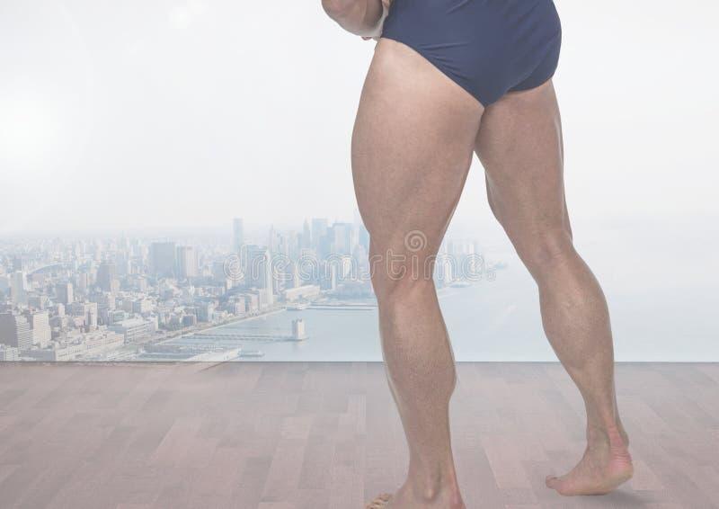 Piernas musculares fuertes del ` s del hombre delante de la ciudad foto de archivo