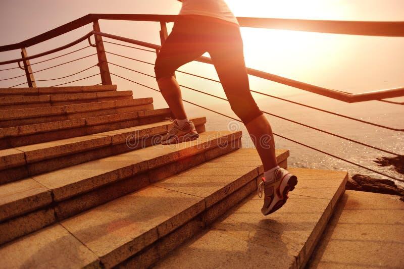 Piernas sanas de la mujer de la forma de vida que corren en las escaleras de piedra imagen de archivo