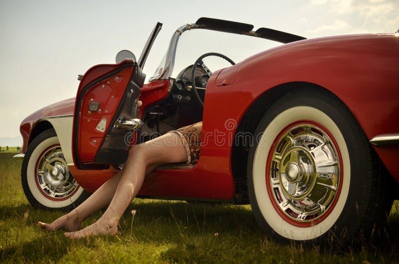 Piernas y coche deportivo atractivos imagen de archivo