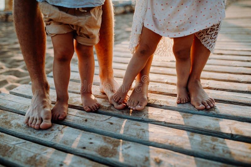 Piernas y pies de la familia que se colocan en la playa el las vacaciones de verano, un midsection fotografía de archivo