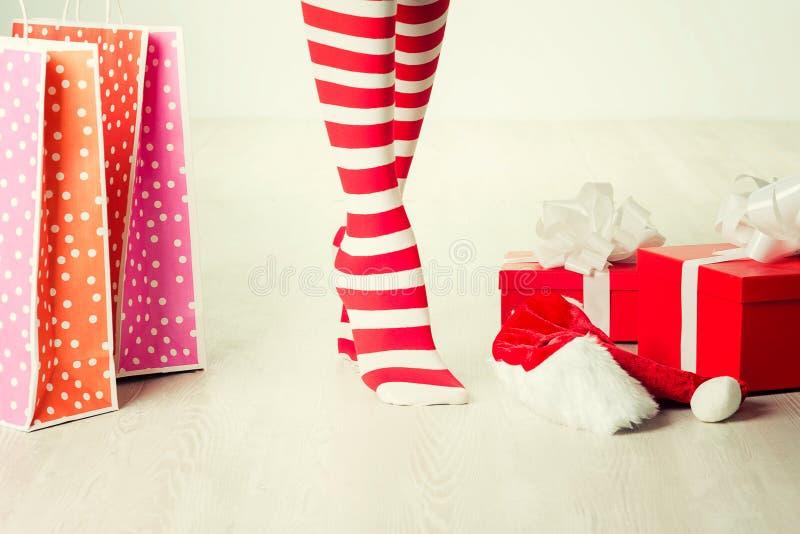 Piernas y regalo de la mujer de Papá Noel Concepto de las compras de la Navidad foto de archivo
