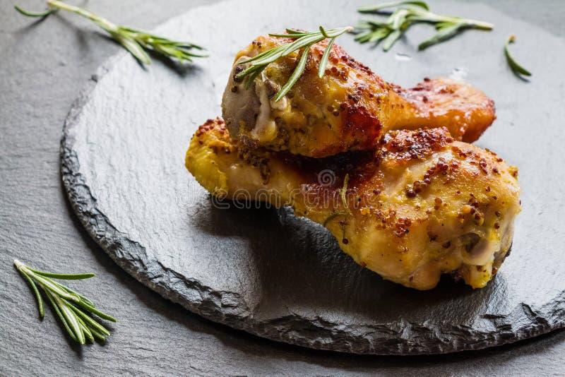 Piernas y romero asados de pollo en el fondo negro foto de archivo