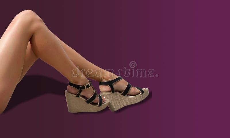 Piernas y sandalias femeninas desnudas foto de archivo
