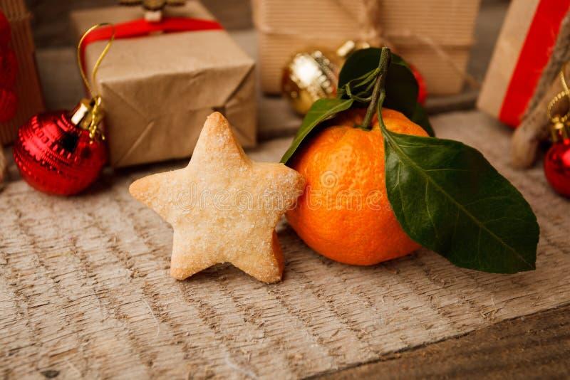 Piernikowa ciastko gwiazda, tangerine z Bożenarodzeniową dekoracją na rocznika drewnianym tle i Bożenarodzeniowy nowego roku zbli zdjęcia stock