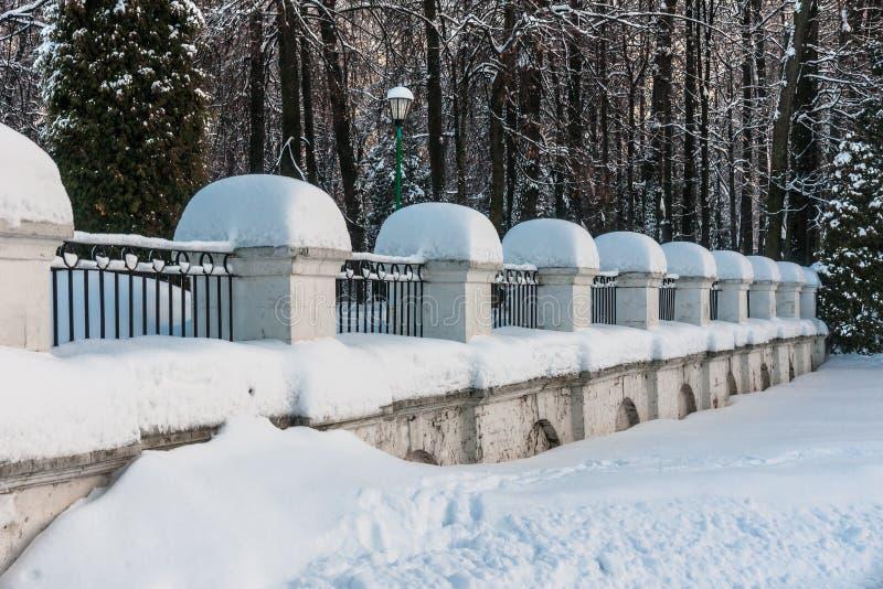 pierre couverte de neige avec la barrière de barres en métal en parc image libre de droits