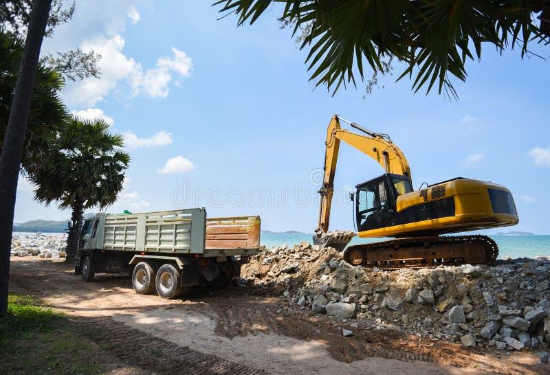 Pierre défonceuse d'excavatrice et camion à benne basculante travaillant au chantier de construction/au chargeur de pelle rétro s photo stock
