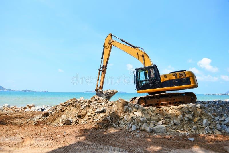 Pierre défonceuse d'excavatrice travaillant au chantier de construction - chargeur de pelle rétro sur le fond d'océan de mer de p photos libres de droits