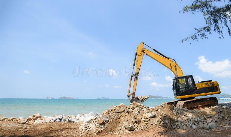 Pierre défonceuse d'excavatrice travaillant au chantier de construction - chargeur de pelle rétro sur le fond d'océan de mer de p photographie stock