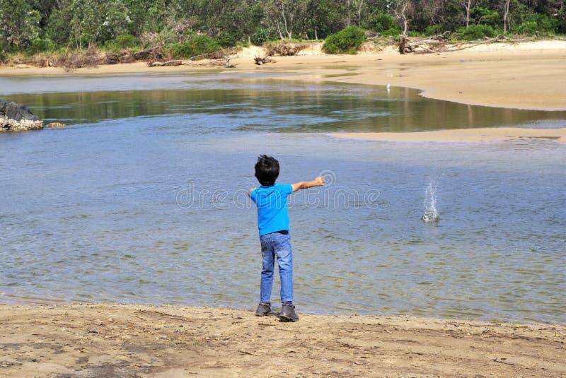 Pierre de lancement d'enfant dans l'eau images libres de droits