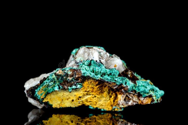 Pierre minérale de malachite crue sur la roche de mère devant le fond noir photo libre de droits