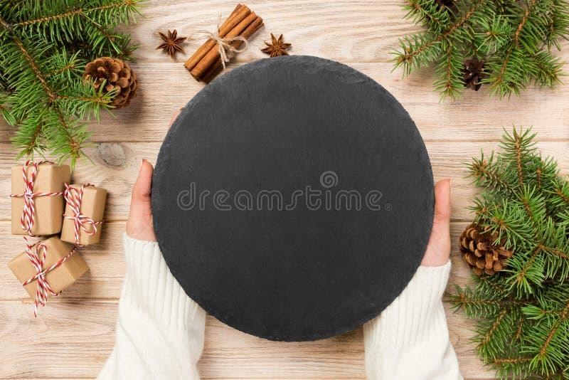 Pierre ronde d'ardoise de noir de prise de main de Famale sur le fond en bois avec la décoration de Noël Vue supérieure, l'espace image stock