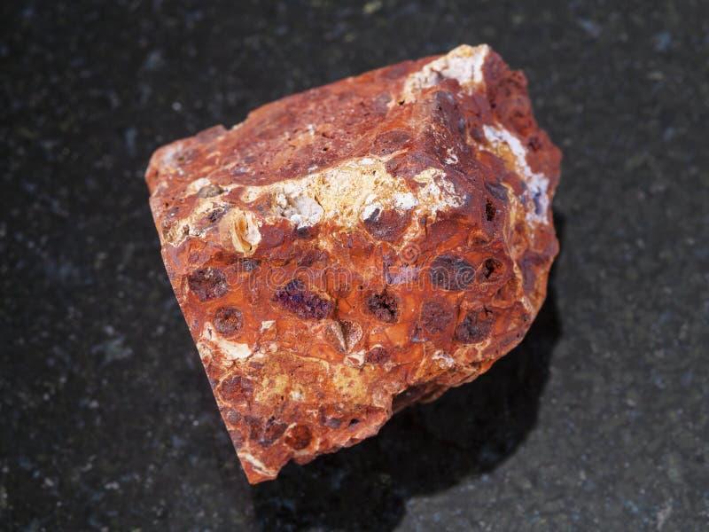 pierre rouge rugueuse de bauxite sur le fond foncé photo libre de droits