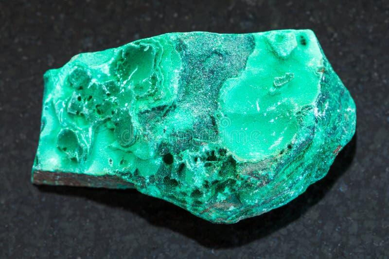 pierre verte rugueuse de malachite sur le fond foncé photo libre de droits