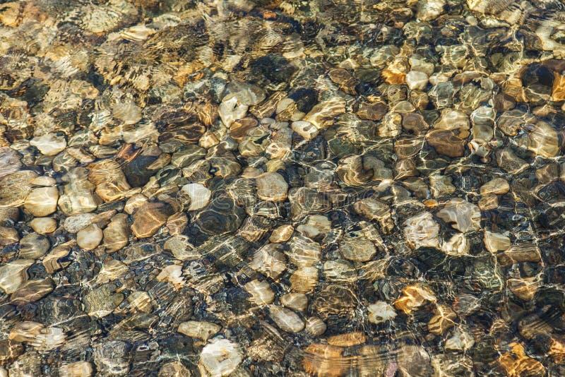Pierres colorées sous l'eau abrégez le fond image libre de droits