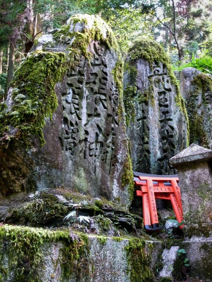 pierres couvertes de mousse gravées avec les caractères chinois chez Fushimi Inari images libres de droits