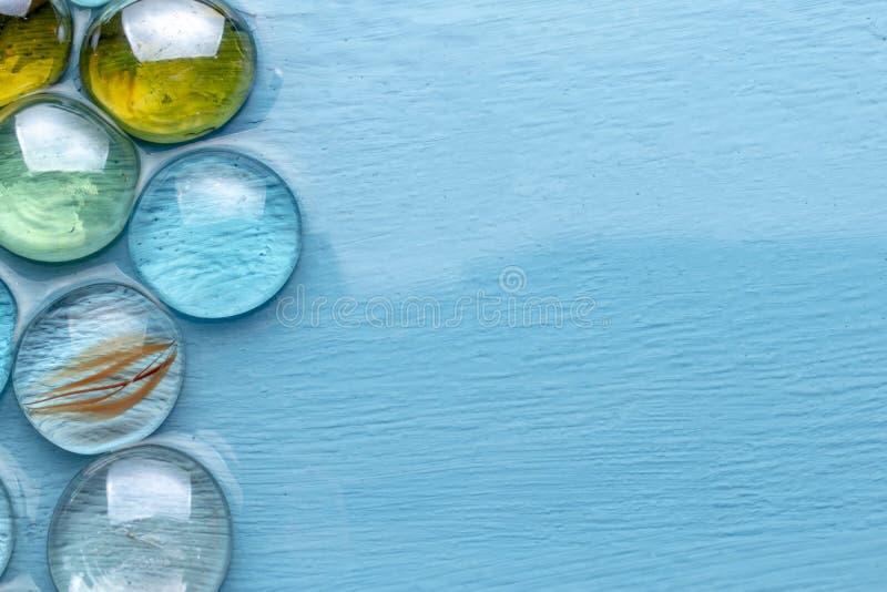 Pierres décoratives de rond en verre sur baisses d'une imitation bleue de fond de grandes Imitation de la mer Saison de vacances image libre de droits