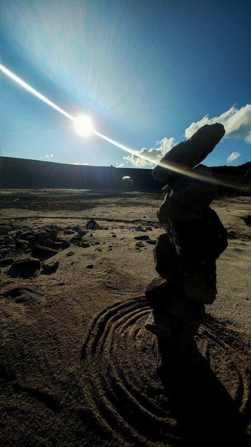Pierres d'équilibre en sable et soleil images stock