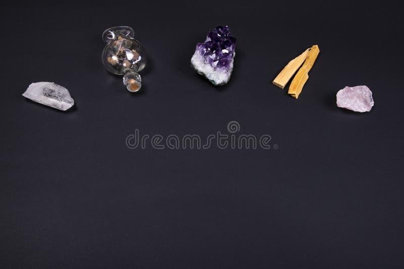 Pierres de cristal d'améthyste et de quartz, bois de santo de palo et bouteille décorative sur le fond noir photographie stock libre de droits