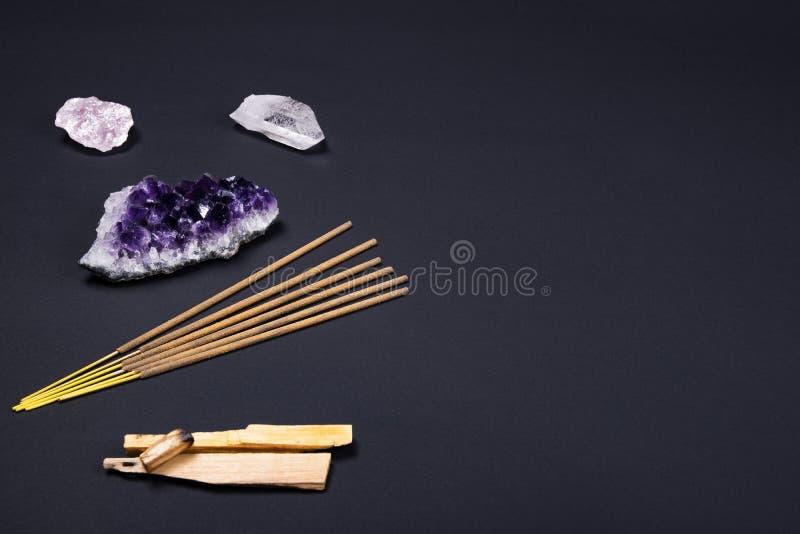 Pierres de cristal d'améthyste et de quartz, santo de palo en bois, bâtons aromatiques sur le fond noir image libre de droits