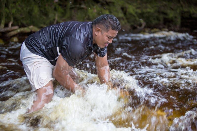 Pierres de levage d'homme fort hors de la rivière, Venezuela image stock